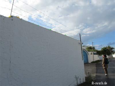 Mauer mit Stacheldraht und Glasscherben